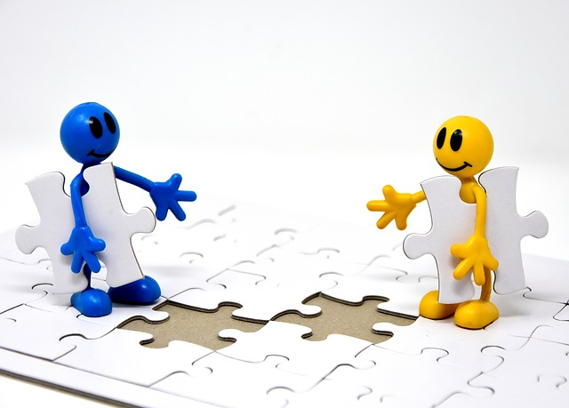 two cartoon characters working together to complete a jigsaw