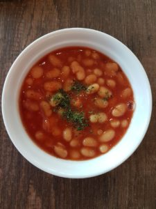 A pot of baked beans with seasoning
